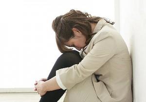膝を抱えて座り込んでいる女性の写真