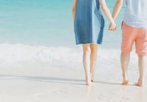 波打ち際で手を繋いだ男女の後ろ姿の写真